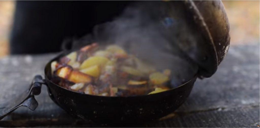 Im Koch-und Brattopf von den alten Holzfällern sind am Lagerfeuer auf Holzkohle besondere Mahlzeiten zu kochen.